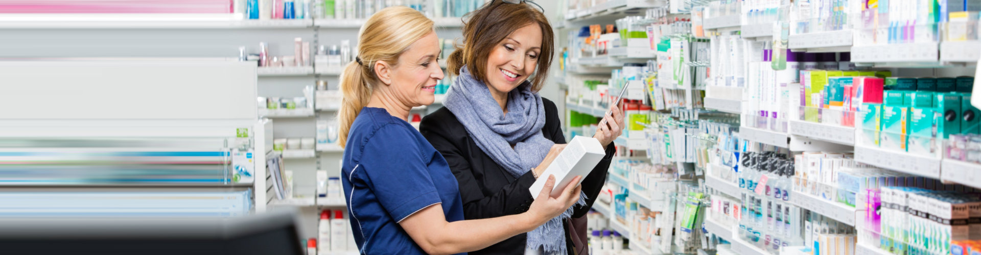 female pharmacist in blue uniform and female customer looking at the medicine box